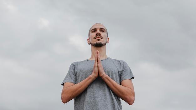 Basso angolo di uomo all'aperto che fa yoga