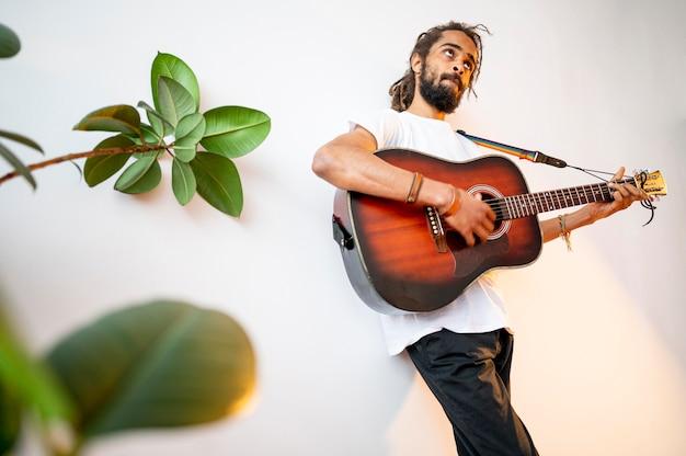 Uomo di angolo basso che gioca la chitarra con lo spazio della copia