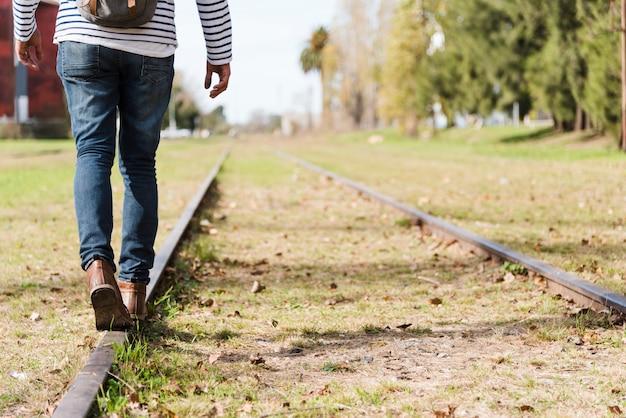 기차 트랙을 걷고 낮은 각도 남자