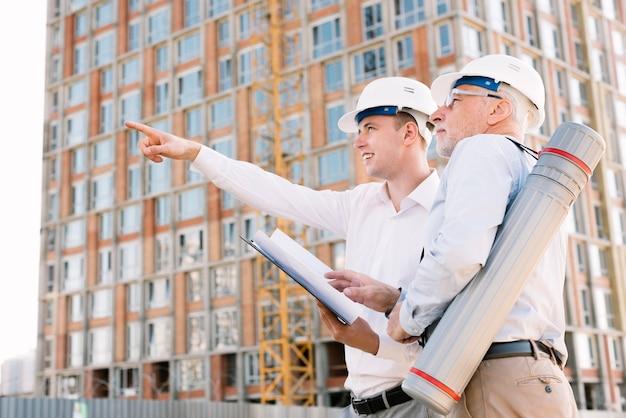 Uomo di angolo basso con il casco che indica a qualcosa Foto Gratuite