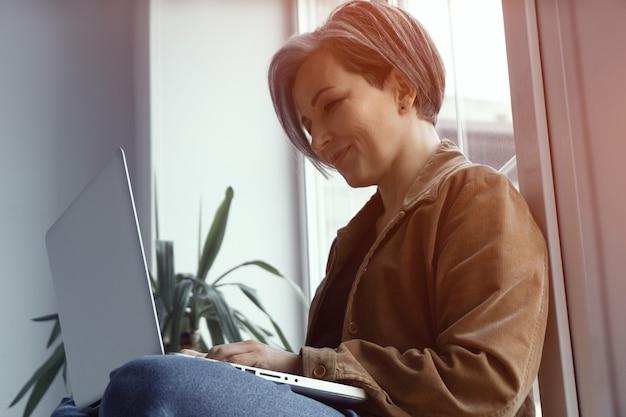 Низкий угол. зрелая женщина улыбается, глядя на чтение портативного компьютера, получив долгожданный контракт сидя