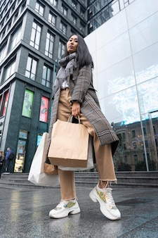 Low angle model holding shopping bags