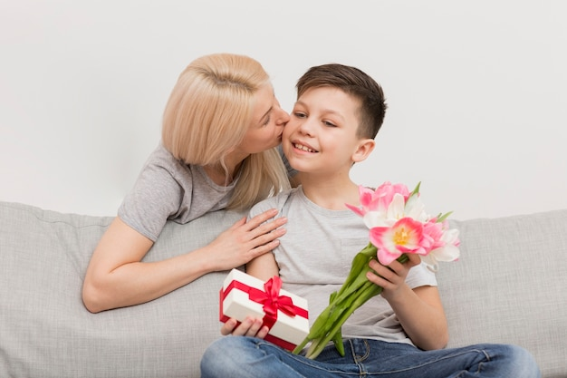 Low angle mother kissing son for gifts