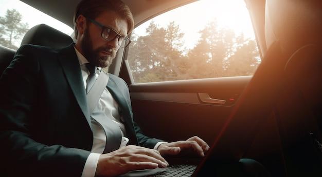 旅行中に車の後部座席に座ってラップトップに取り組んでいる大人の忙しいビジネスマンのローアングル