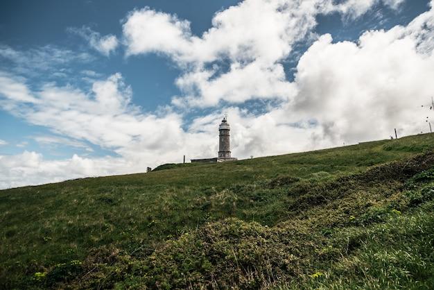 曇った青い空を背景に草が茂った丘の上にある老朽化したカボマヨール灯台のローアングル