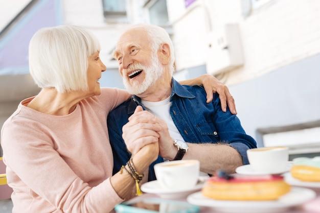 Низкий угол веселой пожилой пары, держащейся за руки и смеющейся
