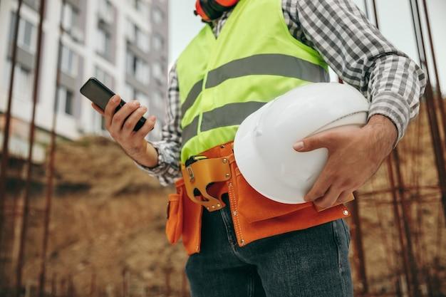 住宅の建設現場に立っている間、スマートフォンでヘルメットをチェックするチョッキの低角度の作物認識できない男性労働者