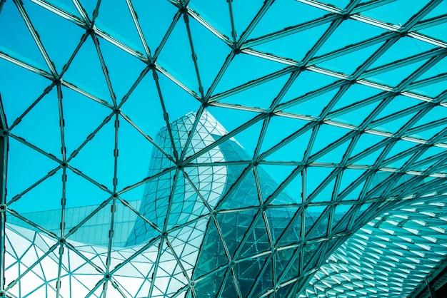 미래 지향적인 스타일로 설계된 현대적인 건물의 기하학적 모양을 가진 곡선 유리 지붕의 낮은 각도