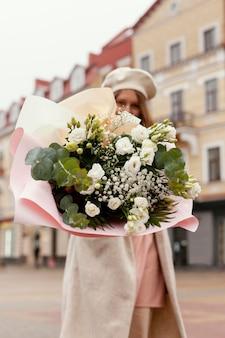 春に花束を持って屋外でエレガントな女性のローアングル