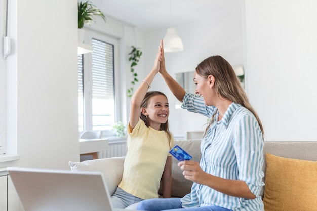 明るいリビングルームのテーブルでラップトップを使用して成功したオンラインショッピングを祝っている間、母親にハイタッチを与え、叫んでいる興奮した小さな娘のローアングル