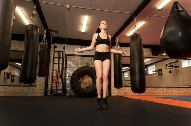 Низкий угол женского боксера, прыжки через скакалку