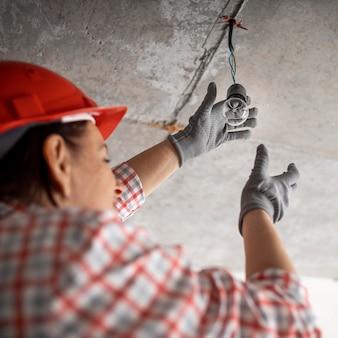 전구를 가진 여성 건설 노동자의 낮은 각도