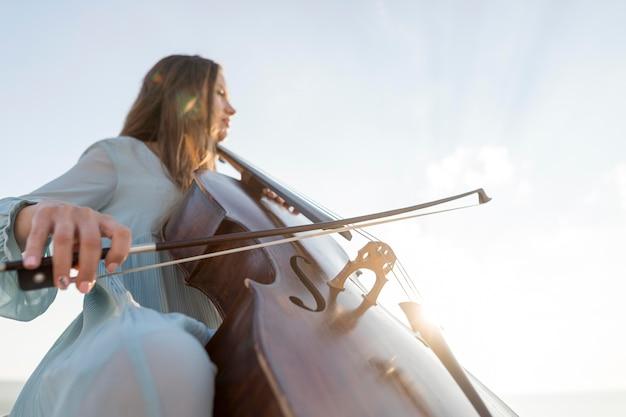 コピースペースでチェロを演奏する女性ミュージシャンのローアングル