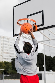 Низкий угол девушка бросает в баскетбольное кольцо