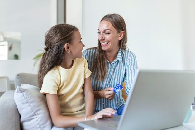 画面に焦点を当て、明るいモダンなアパートでオンラインショッピングにラップトップを使用してカジュアルな服を着て母親を笑顔しながら喜んで幸せな小さな娘のローアングル