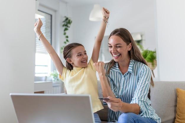 画面に焦点を当て、明るいモダンなアパートでオンラインショッピングにラップトップを使用してカジュアルな服を着て母親を笑顔しながら喜んで腕を上げた幸せな小さな娘のローアングル
