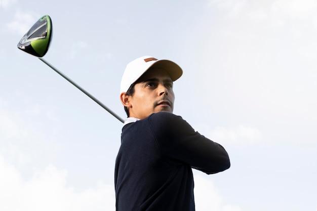 Низкий угол человека с клюшкой для гольфа