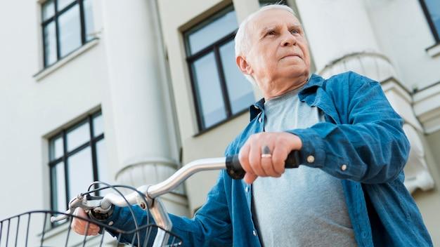 Низкий угол старика с велосипедом