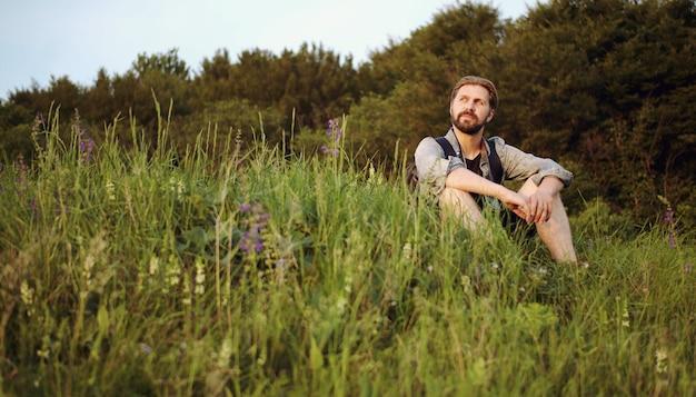 春や夏の自然を楽しむ森の端の草の上に座っているアウトドアマンのローアングル