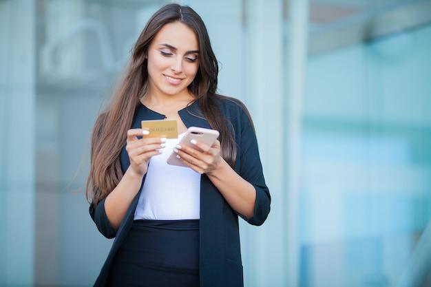 空港ホールに立っている喜んでいる女の子のローアングル。彼は支払いにゴールドクレジットカードと携帯電話を使用しています