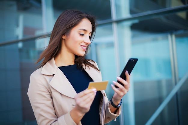 空港ホールに立っている喜んでいる女の子のローアングル彼は支払いに金のクレジットカードと携帯電話を使用しています