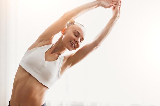 自宅の明るい部屋でのトレーニングの前にウォーミングアップしながら、スポーツトップストレッチアームでポジティブな若いフィットの女性のローアングル