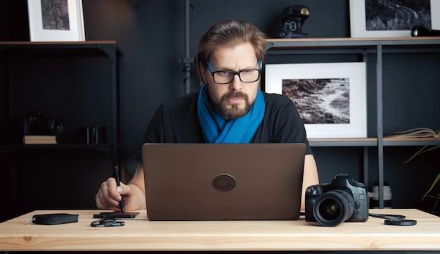 写真編集アプリケーションで作業している写真をレタッチするプロの写真家のローアングル
