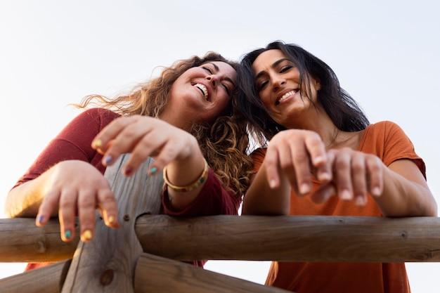 屋外の笑顔の女性の友人の低角度
