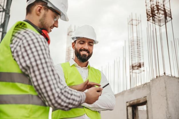 建設現場でプロジェクトについて話し合っている間、携帯電話のアプリを使用してヘルメットとチョッキで笑顔の多民族の男性の同僚の低角度