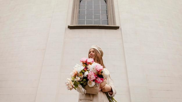 春に花束を持って屋外でスタイリッシュな女性のローアングル