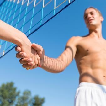 해변 손에 배구 선수의 낮은 각도 그물 아래 흔들