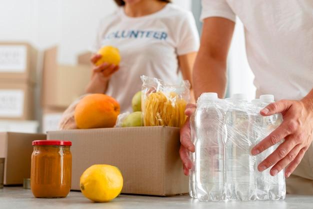 寄付のための食糧を準備するボランティアの低角度