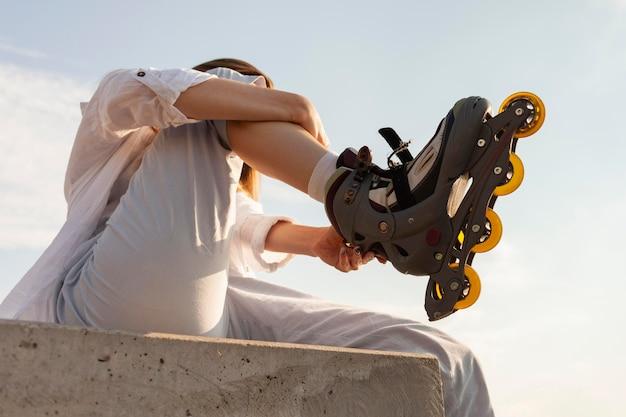 彼女のローラーブレードを調整する女性のローアングル