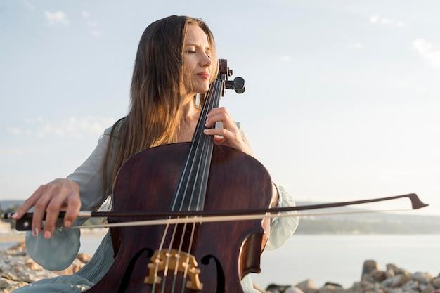 岩の上でチェロを演奏する女性のローアングル