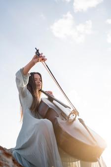 コピースペースでチェロを演奏する女性のローアングル