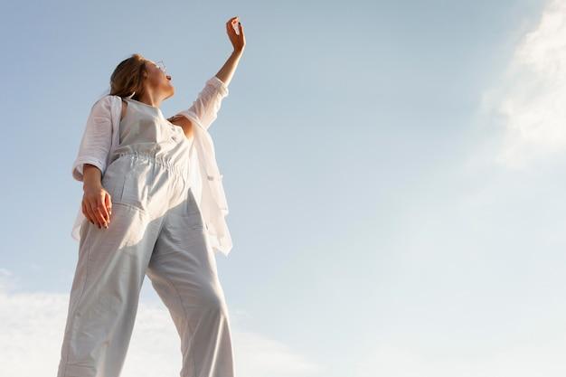 澄んだ空と太陽の下でポーズをとる女性のローアングル