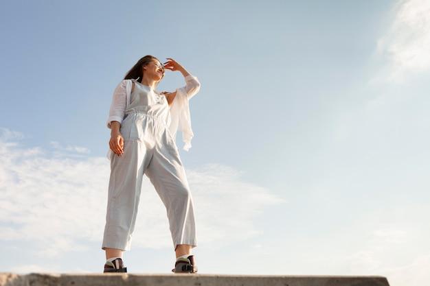 Низкий угол женщины, позирующей на открытом воздухе с копией пространства