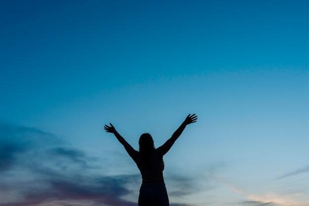 Низкий угол силуэта женщины на закате с копией пространства