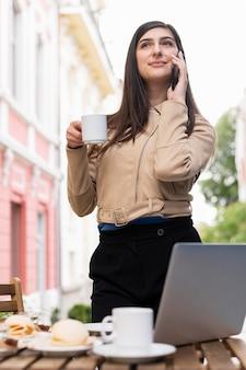 働くとランチとコーヒーを持っている女性の低角度