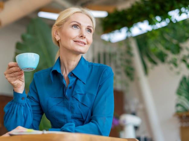 Basso angolo di donna più anziana di affari che mangia una tazza di caffè mentre si lavora