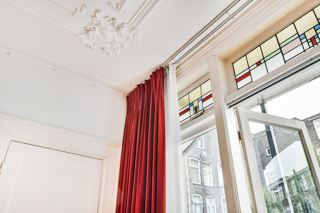 Low angle of ornate white stucco molding on ceiling in classic style room with vintage window and curtain