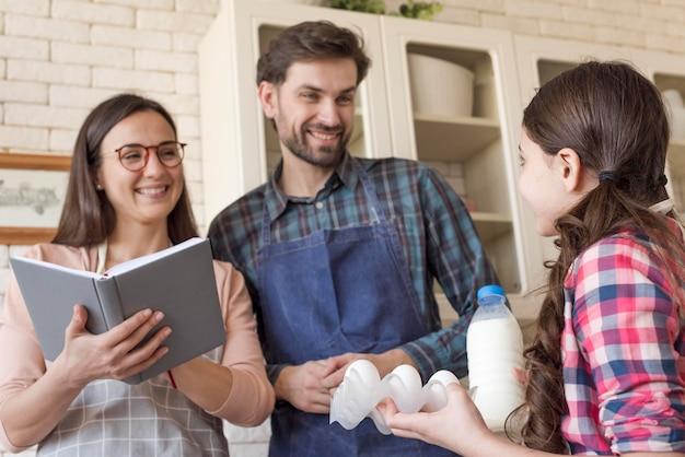 調理する女の子を教える低角度の両親