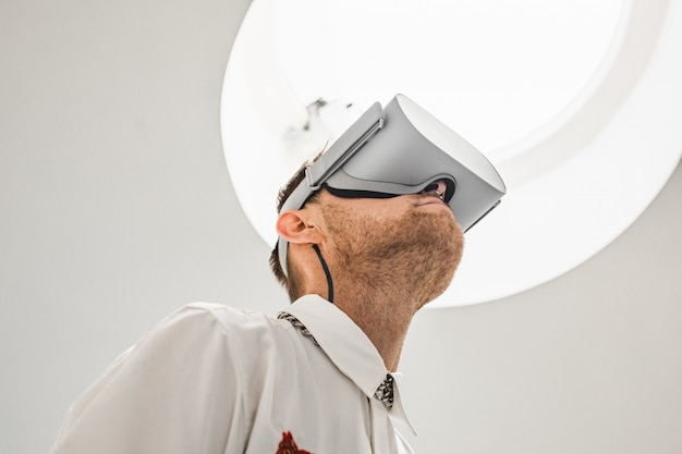 A low angle photo of a futuristic cool male doctor wearing vr goggles in a hospital