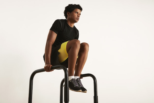 Low angle photo of a strong muscular lean black male model with an afro in black workout clothes rising knees on parallel bars isolated on white.