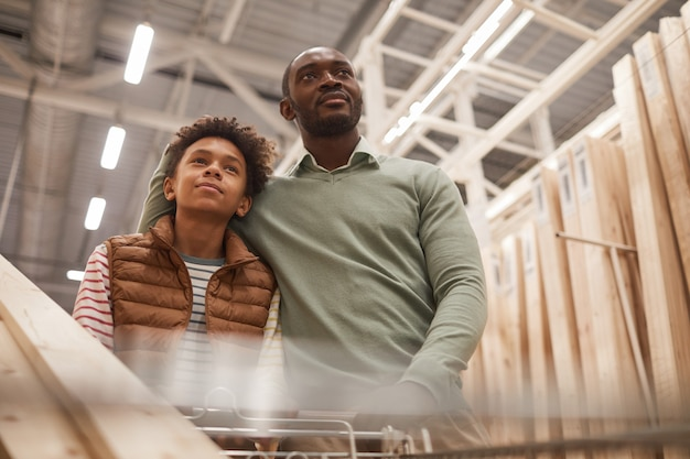 Low angle portrait of african-american father and son shopping together in hardware store while pushing cart with wooden boards for construction or home improvement