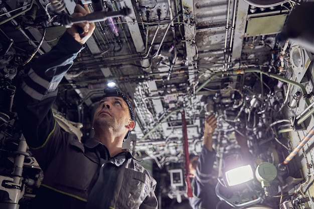 Low angle portrait of aviation mechanic working inside aircraft wearing typical working gear like an overall