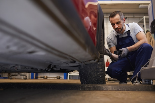 Low angle portrait of bearded car mechanic checking pressure in tires during vehicle inspection in garage shop, copy space