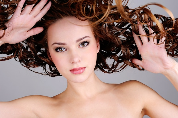 Low angle portrait of the beautiful woman with long curly hairs
