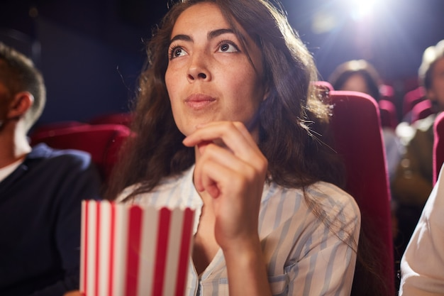 Low angle portrait of beautiful young woman eating popcorn in cinema while enjoying movie alone, looking up at screen