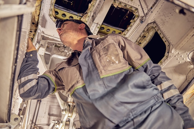 Low angle portrait of confident responsibility engineer in overall uniform is checking different system inside the passenger aircraft